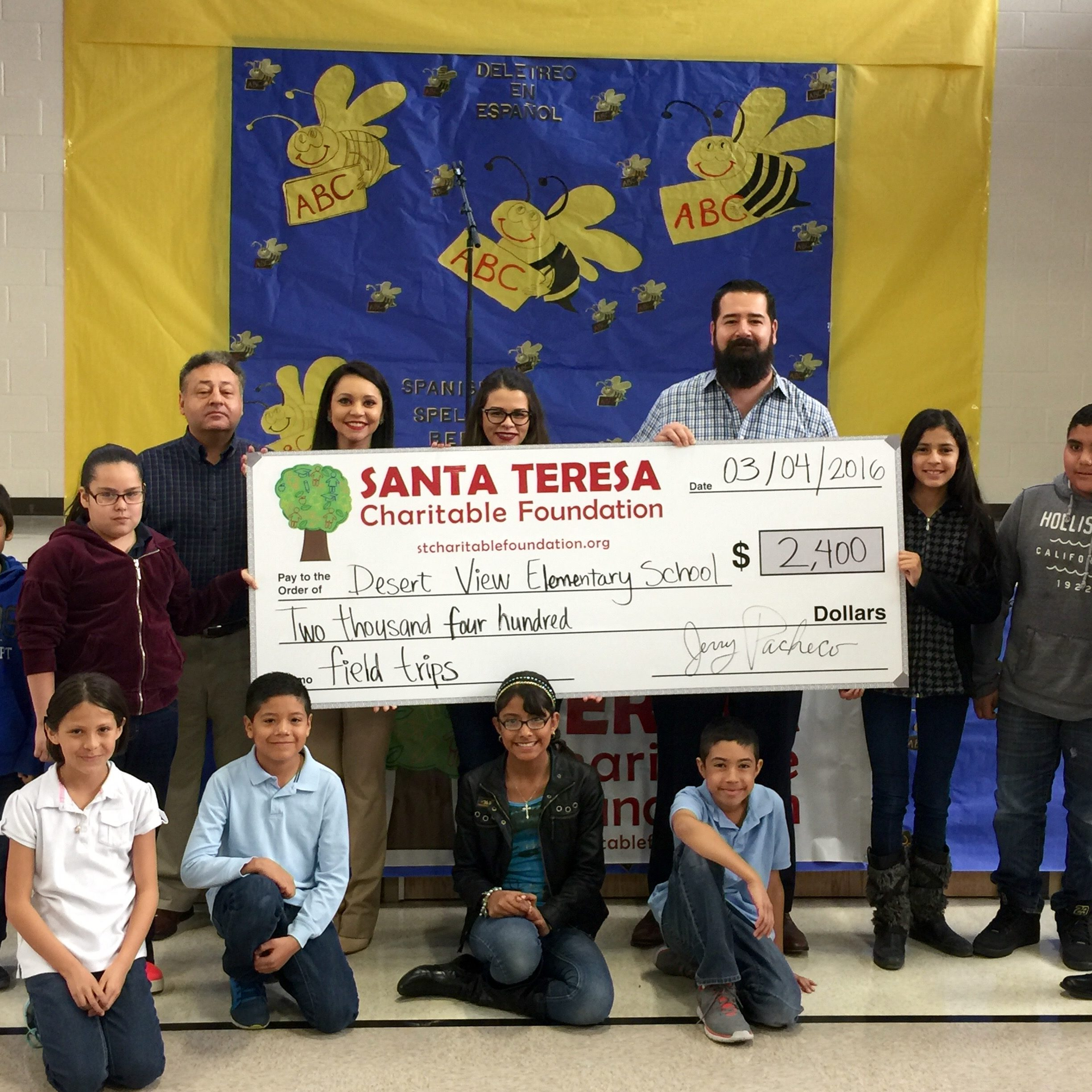 Jerry Pacheco, Adriana Castillo, Ilse Arreola and Joshua Orozco of the STCF present a check to Desert View Elementary School Principal Jorge Araujo and students.